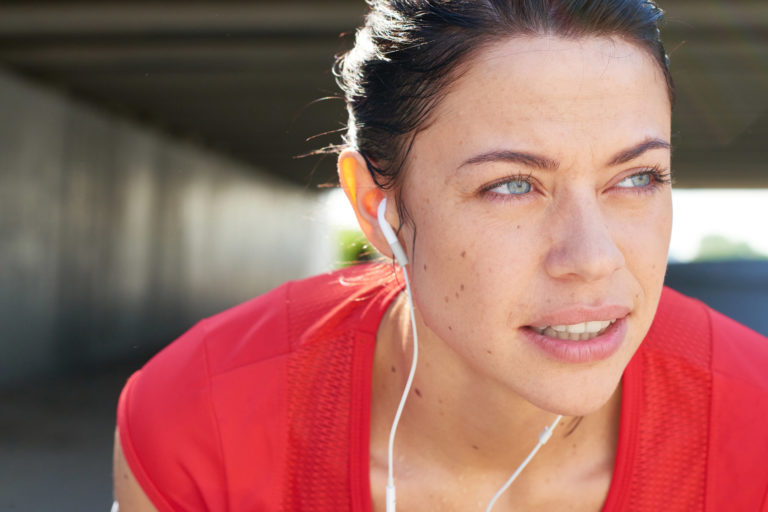 woman in a red shirt resting during a jog