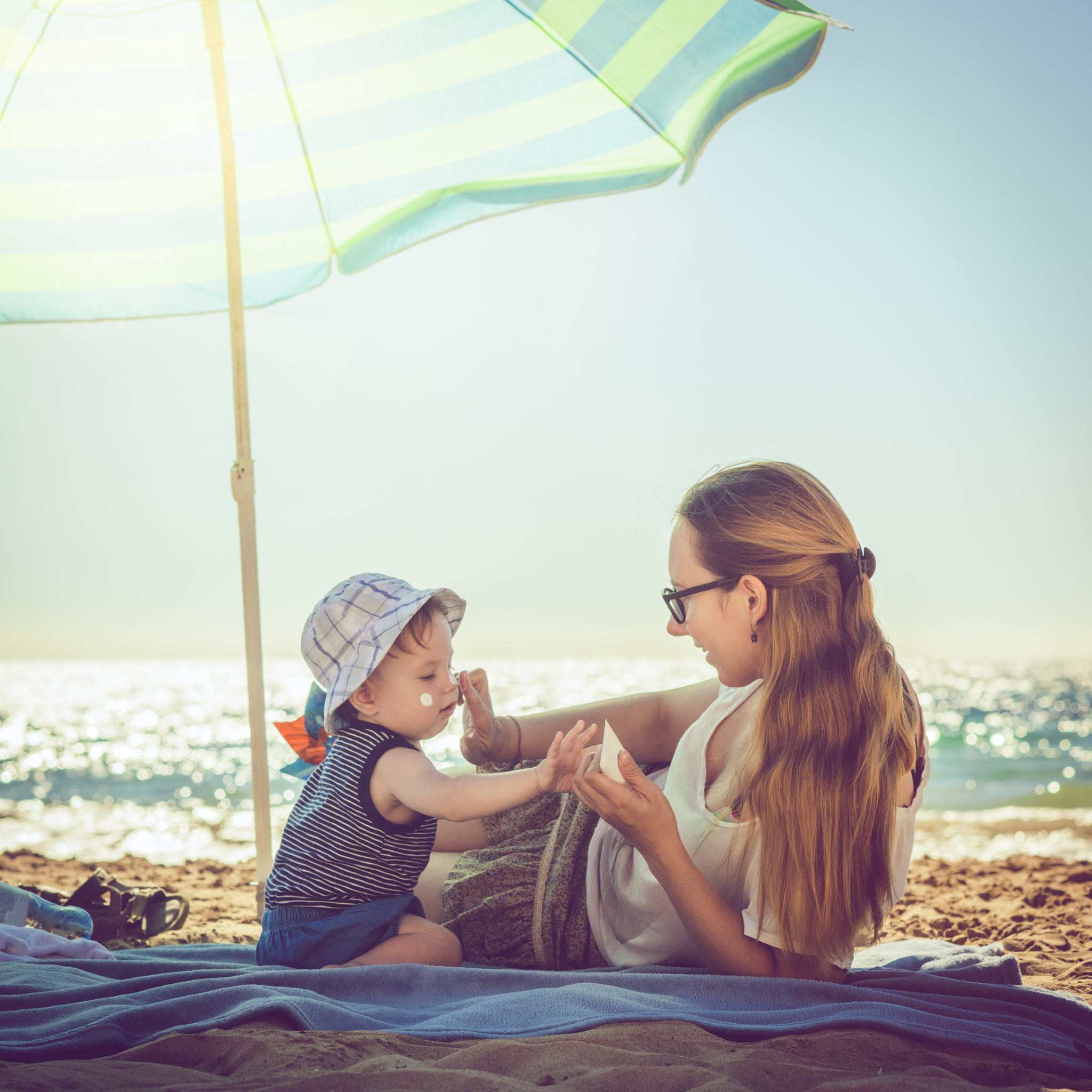 Young mother applying sunblock cream on her baby boy at the beach