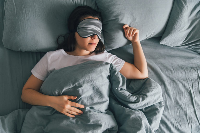 woman sleep in eye patch in grey bed