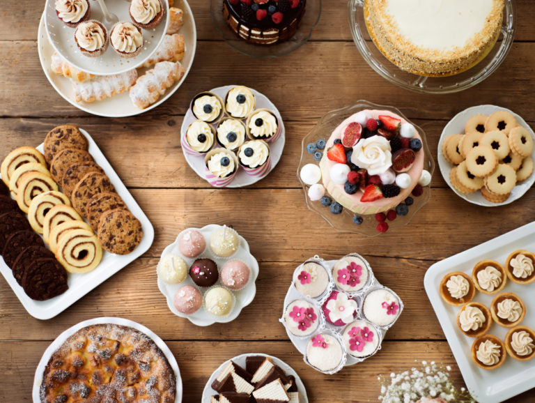 Table with cakes, cookies, cupcakes, tarts and cakepops.