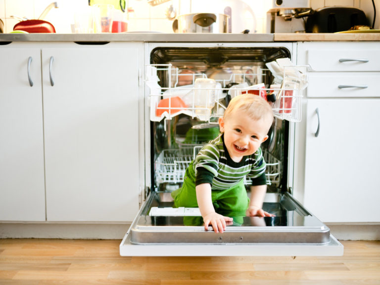 little boy climbing in dishwasher