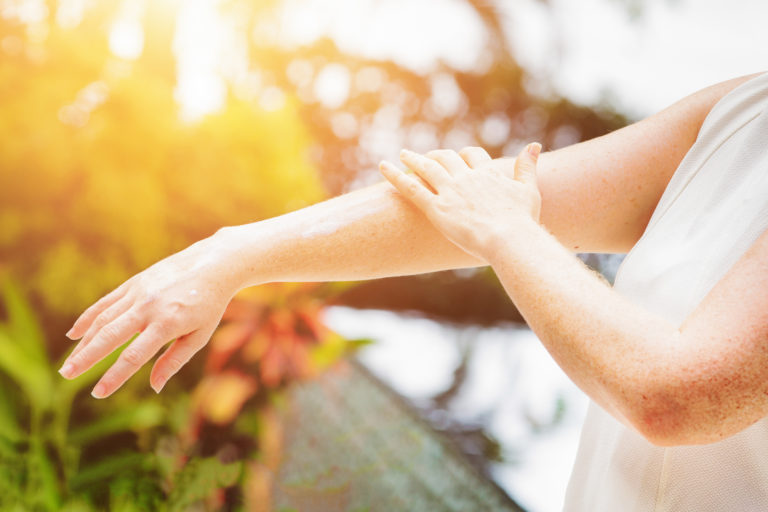 woman-applying-sunscreen-arm