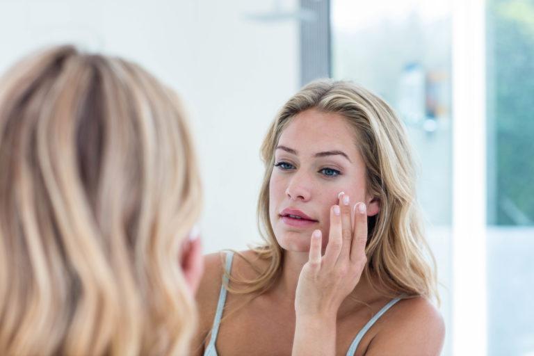 woman-applying-sunscreen-mirror