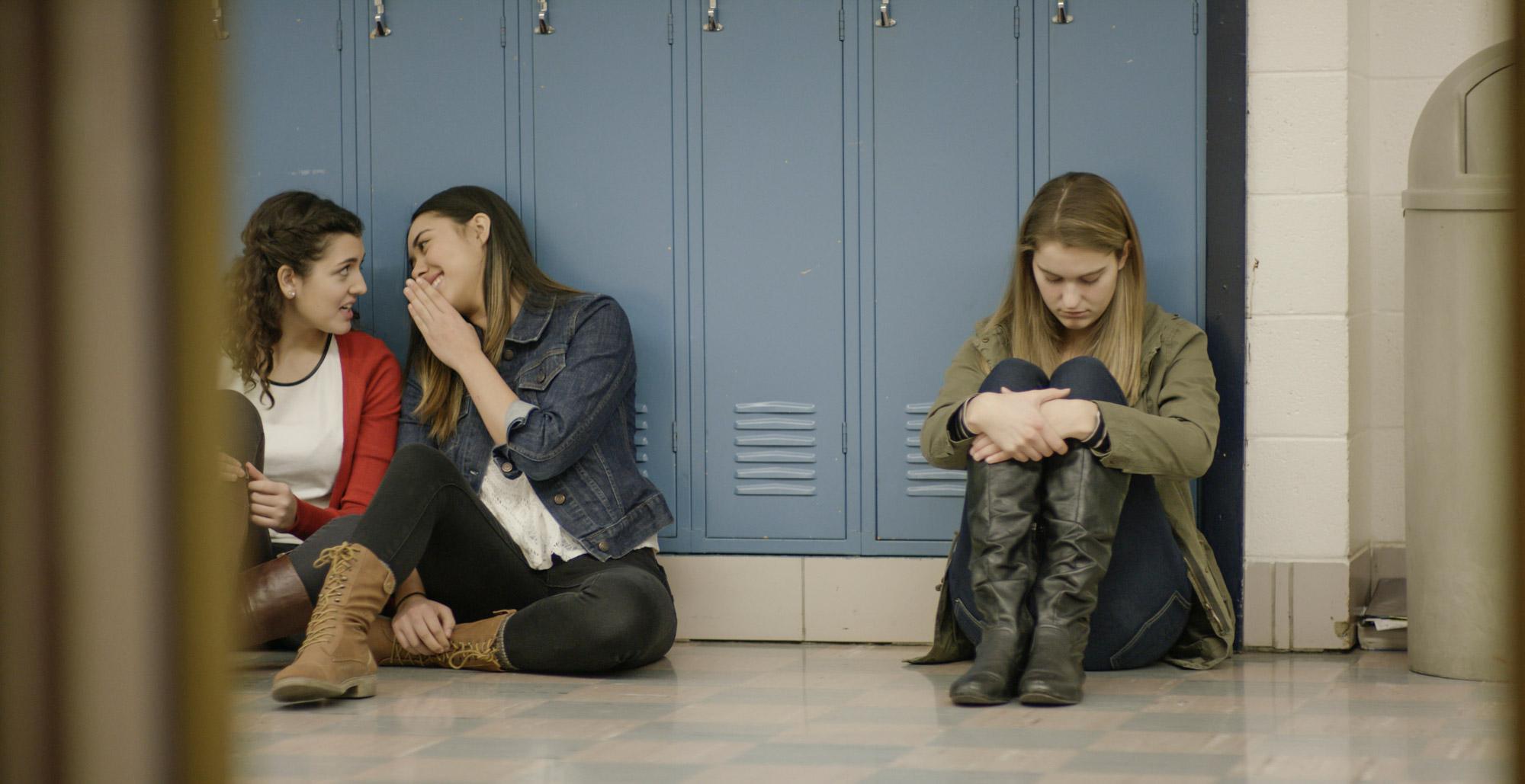 girls whispering at a locker