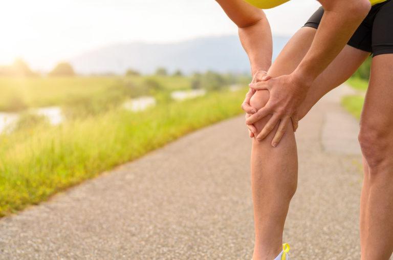 female runner holding her knee