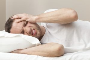 Portrait of Young Caucasian man in bed with headache