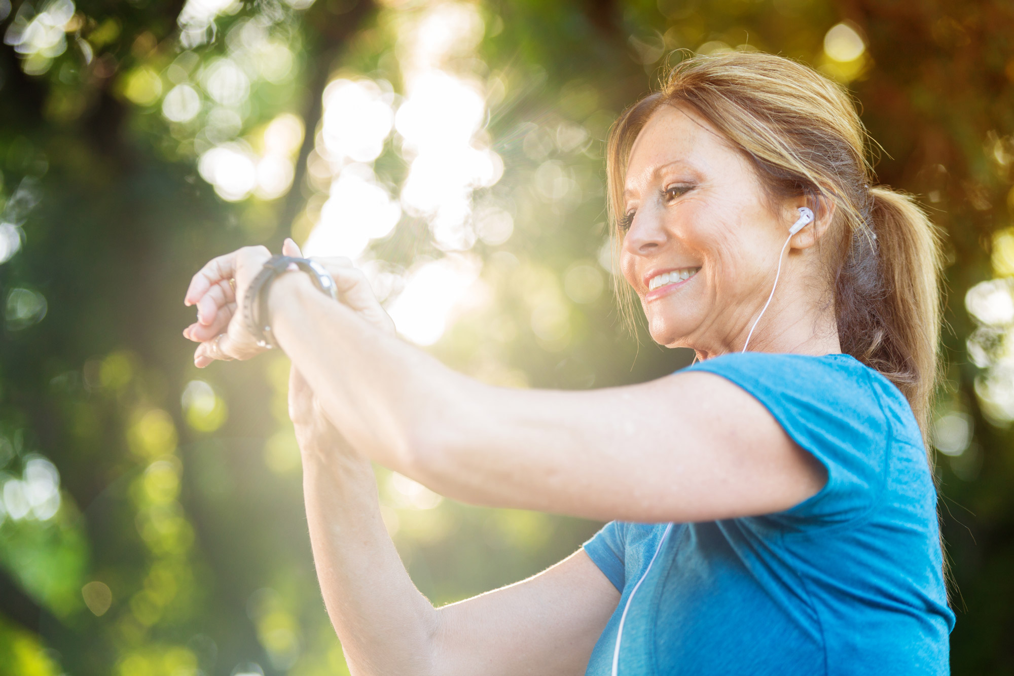 woman exercising and looking at fitness tracker