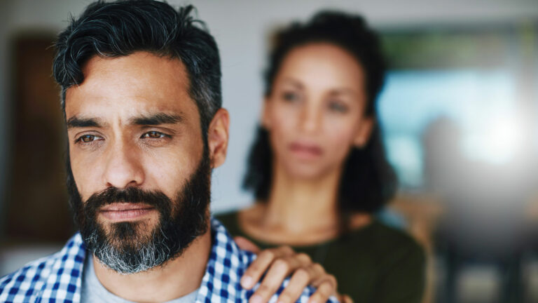 Woman supporting man with grief or mental illness