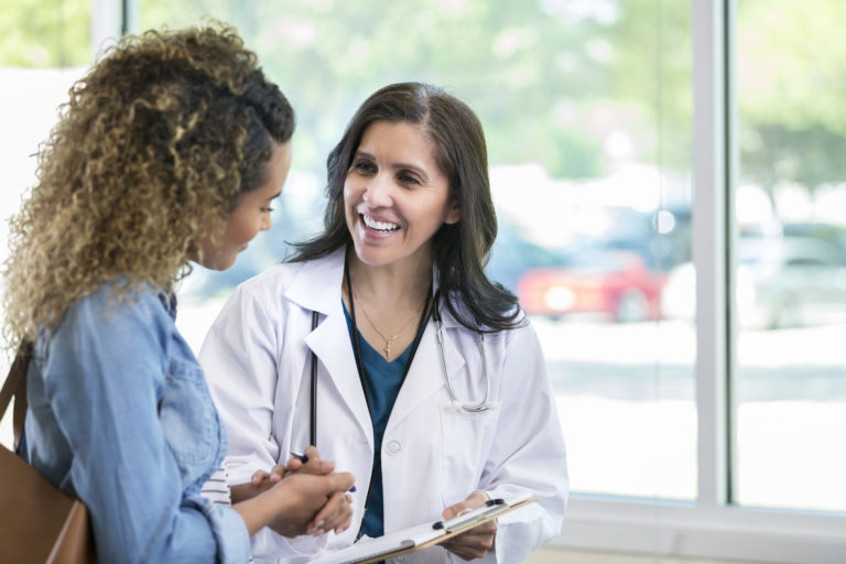 Female doctor discusses something with young mixed race patient