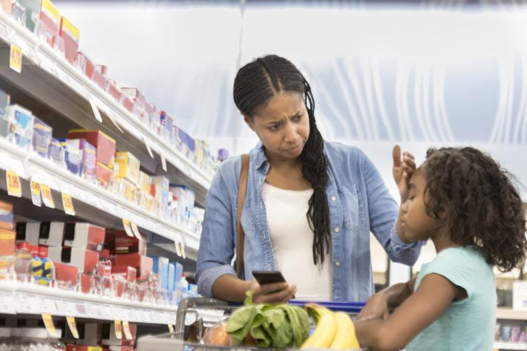 Mother checks daughter for fever in supermarket pharmacy