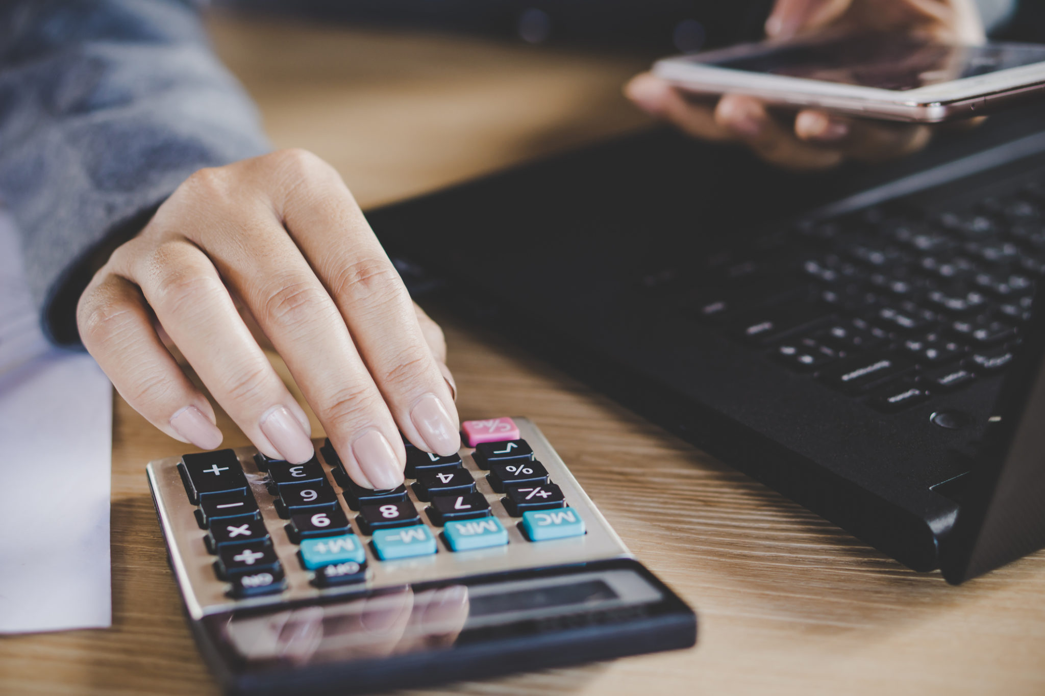 businesswoman hand calculating while working on computer laptop