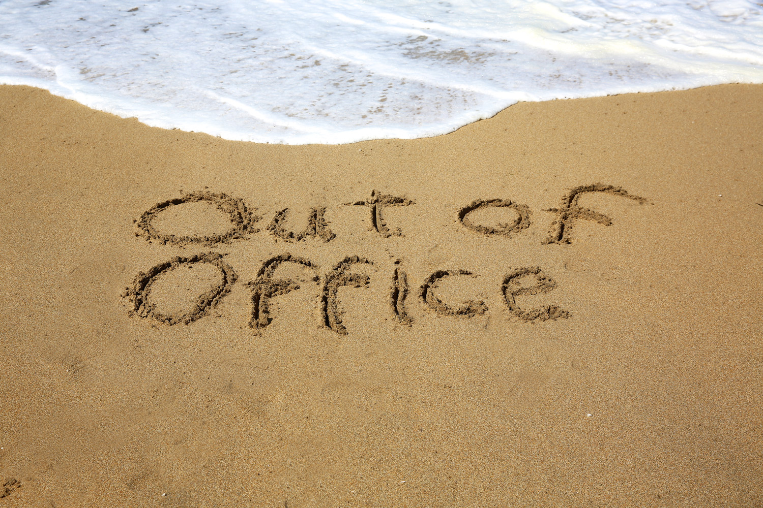 out of office written in the sand