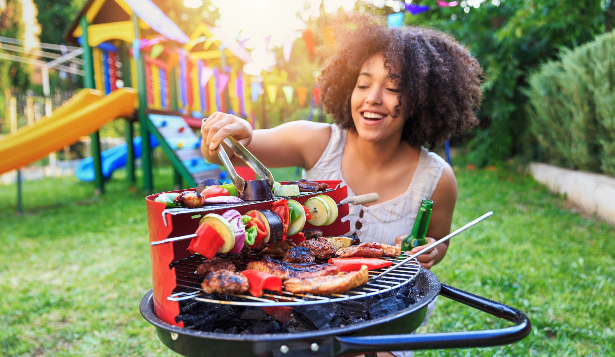 Smiling woman preparing barbecue at backyard