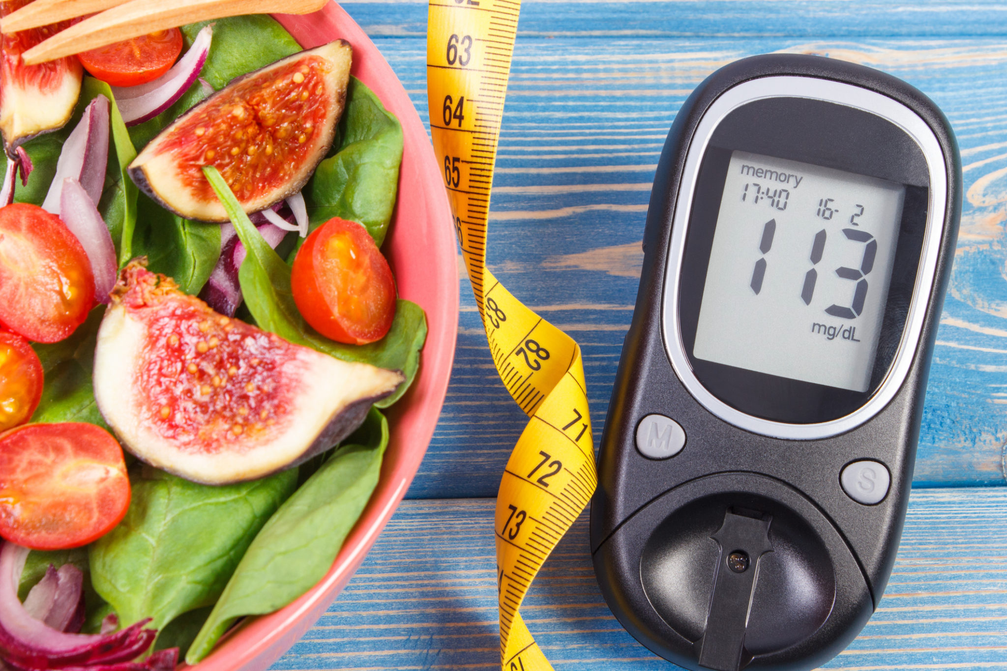 Fruit and vegetable salad and glucose meter with tape measure, concept of diabetes, slimming and healthy nutrition