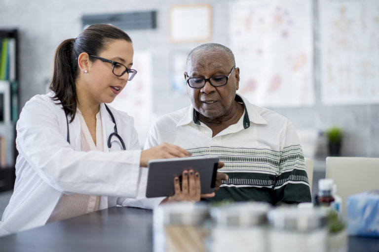 Doctor With A Tablet Computer talking to elderly male patient