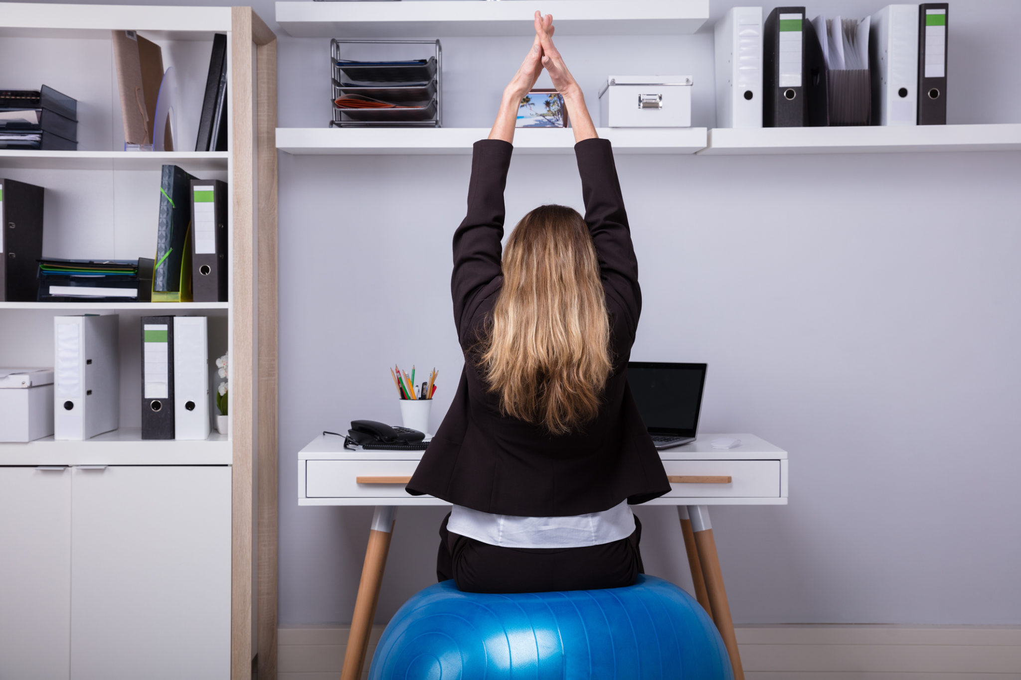 Rear View Of A Businesswoman Stretching Her Arms