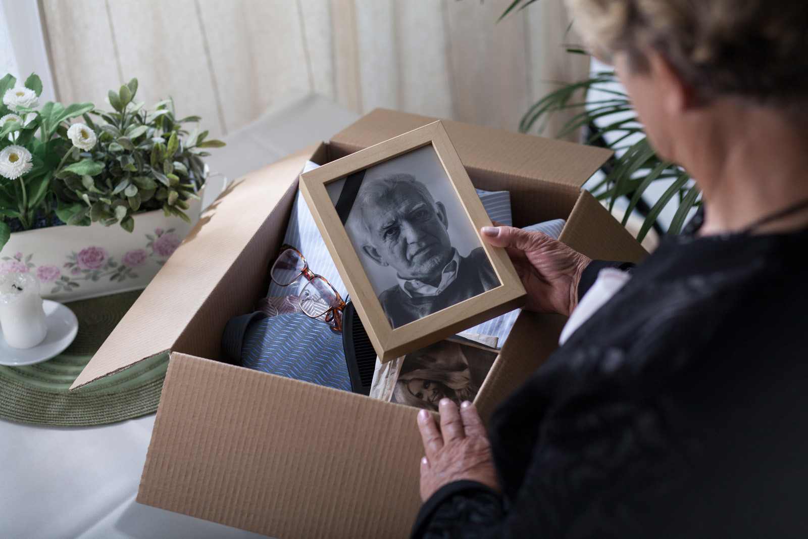 Older woman looking in a box of things and holding a black and white photo of an old man