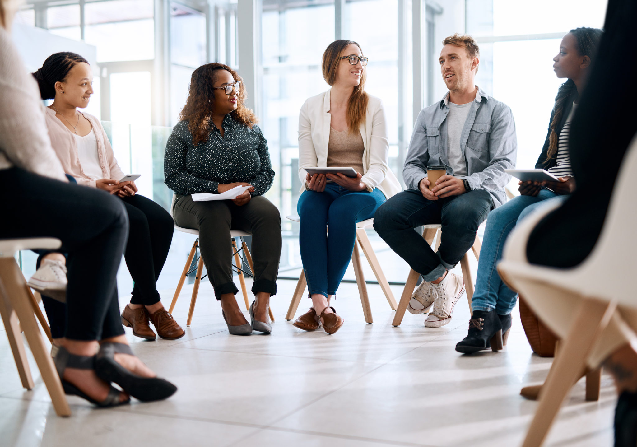 Shot of a group of people in a circle talking with eachother, they could be in a support circle or they could be having a meeting