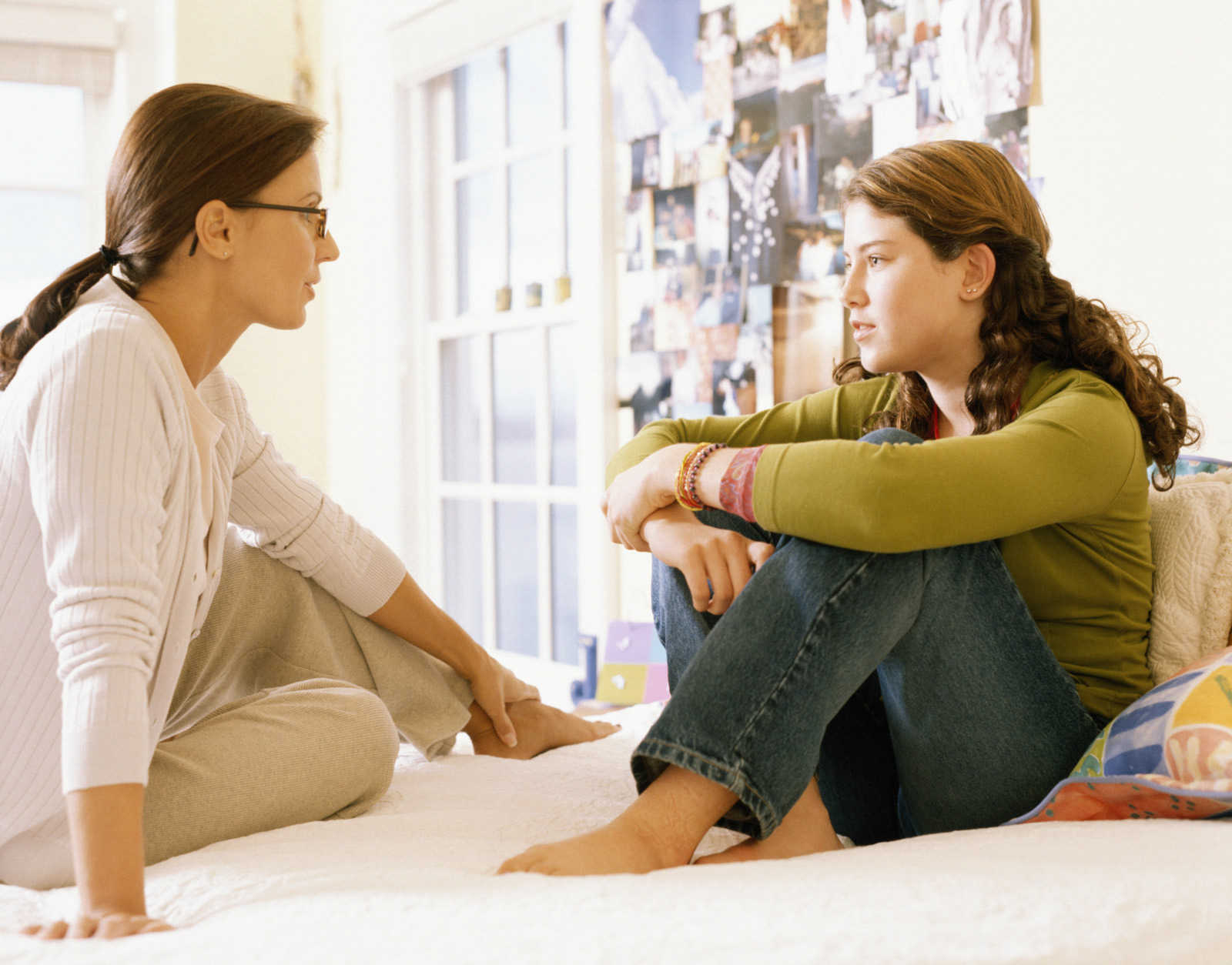 Mother talking with teenage daughter on a bed in bedroom