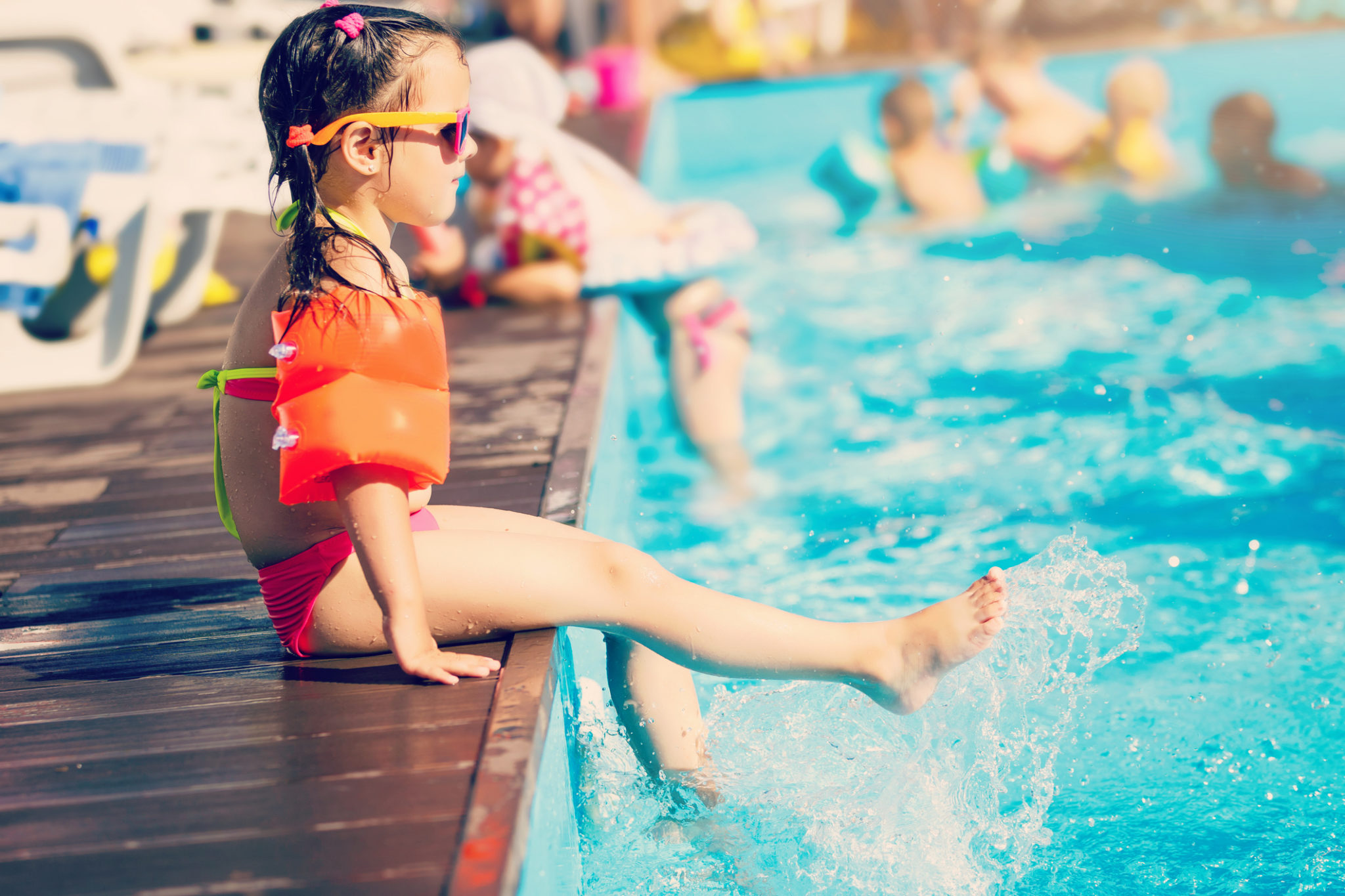 Little girl playing in outdoor swimming pool jumping into water on summer vacation on tropical beach island. Child learning to swim in outdoor pool of luxury resort.