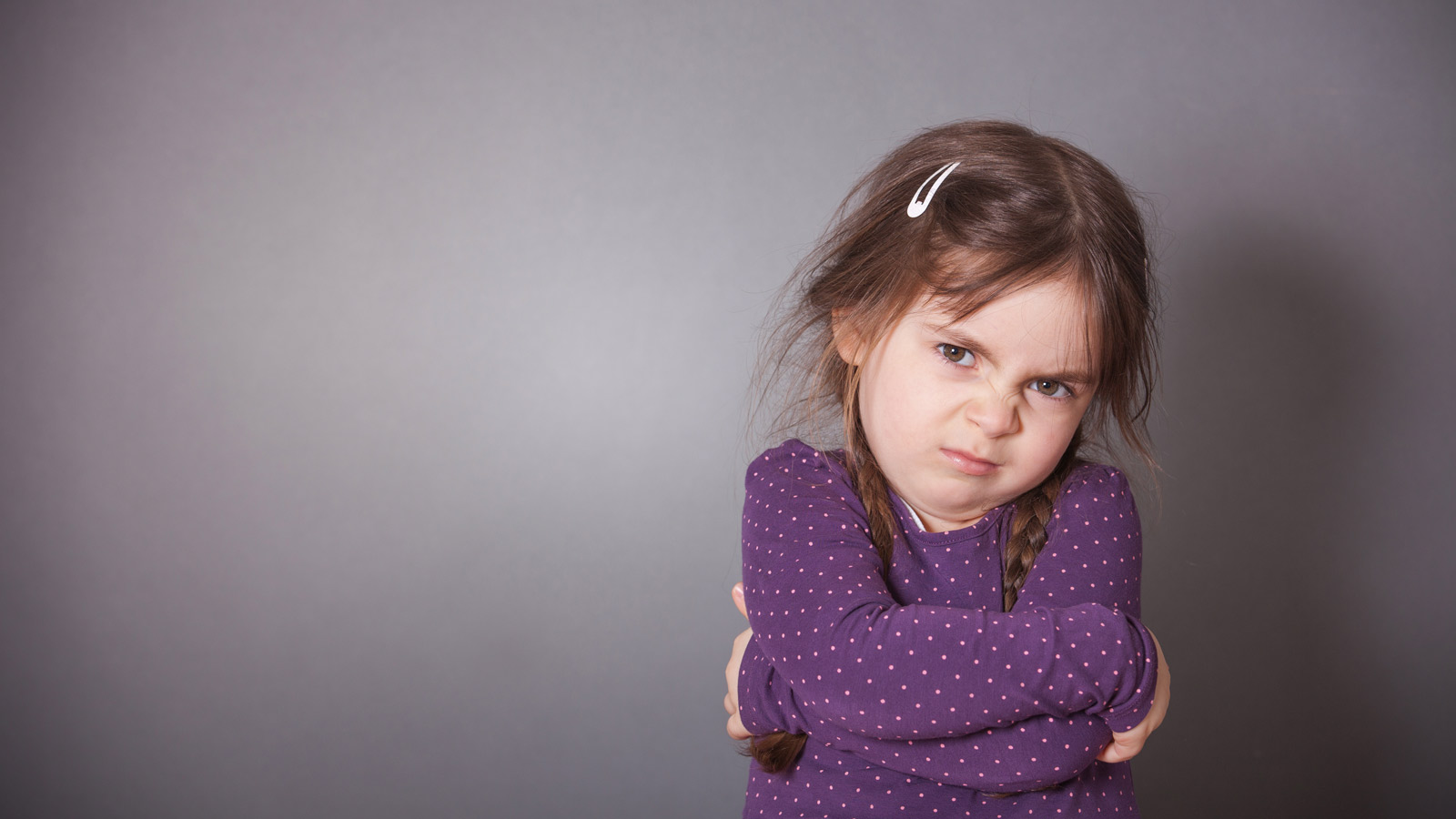 mad toddler girl in a purple shirt