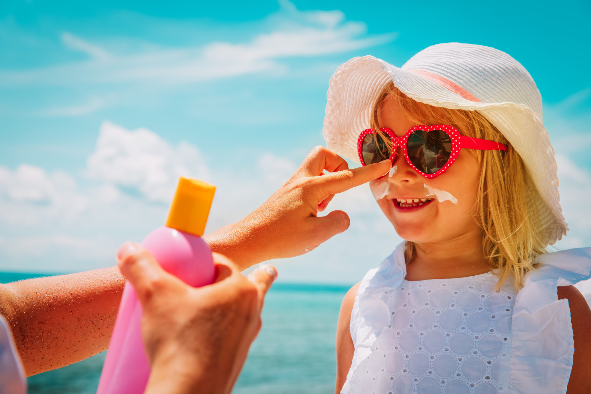 mother putting sunblock cream on little daughter face at beach