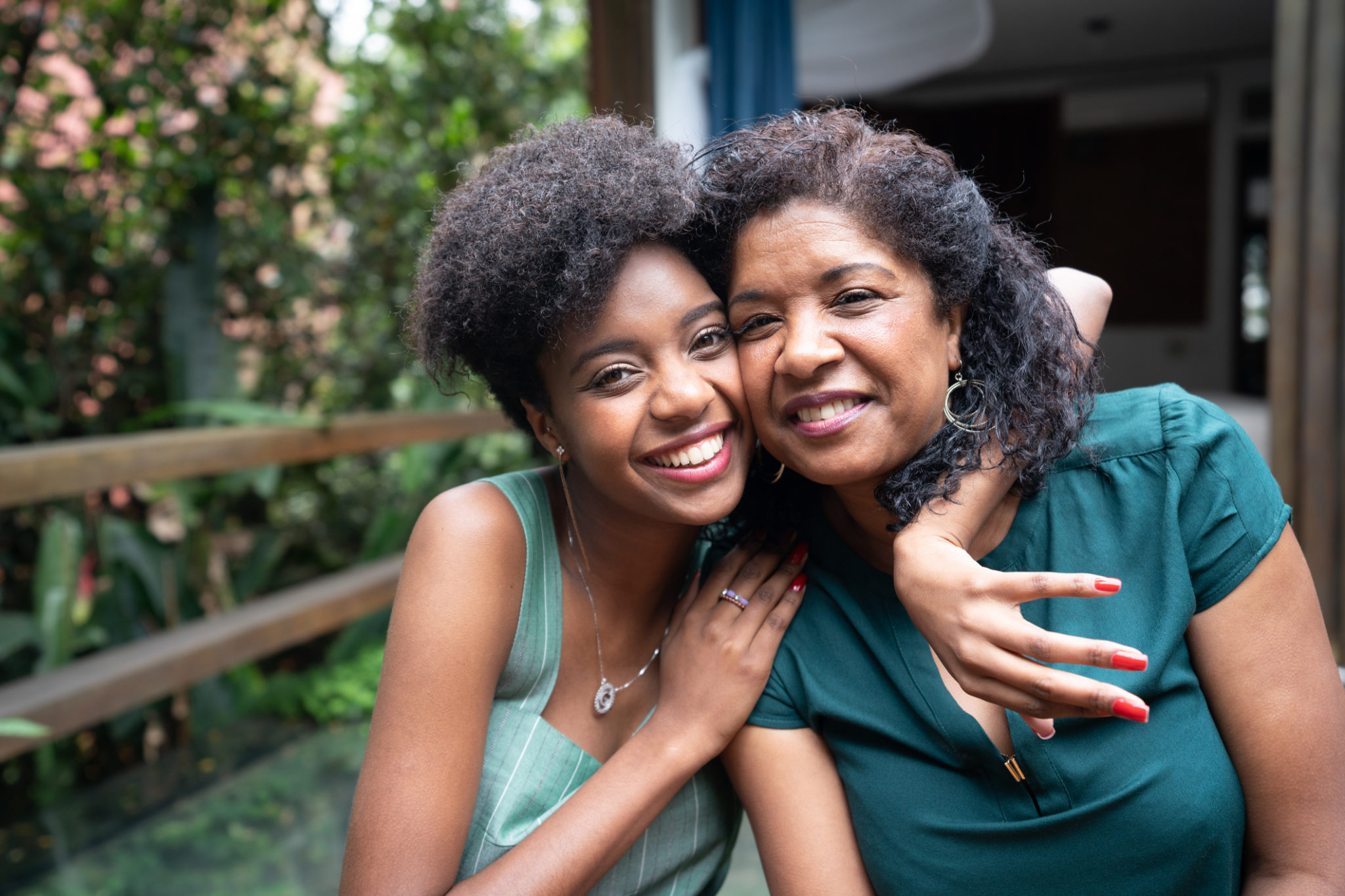 African American Mother and Daughter Embracing outside on a deck, smiling at the camera