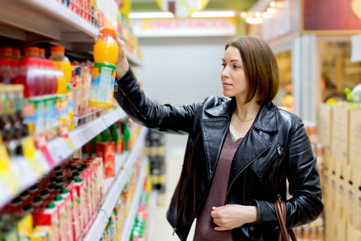 woman in a supermarket buying a bottle of juice