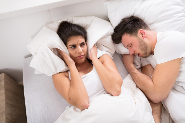 An Angry Woman With Snoring Husband On Bed