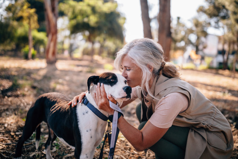 Fashionable senior woman kissing pet dog in nature