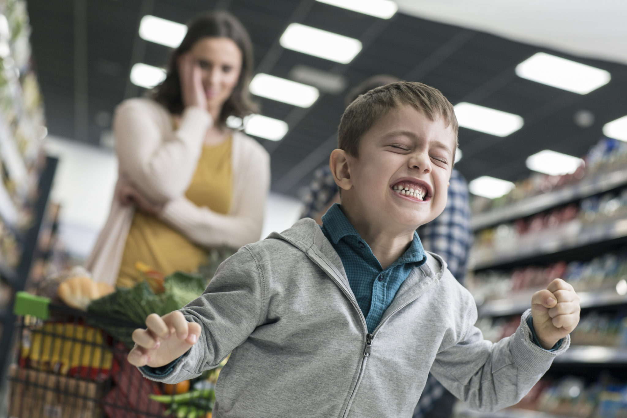 Young boy in supermarket who is having a tantrum