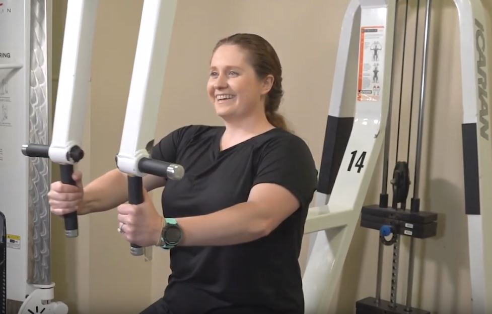 Lady demonstrating how to use a pec fly weight machine