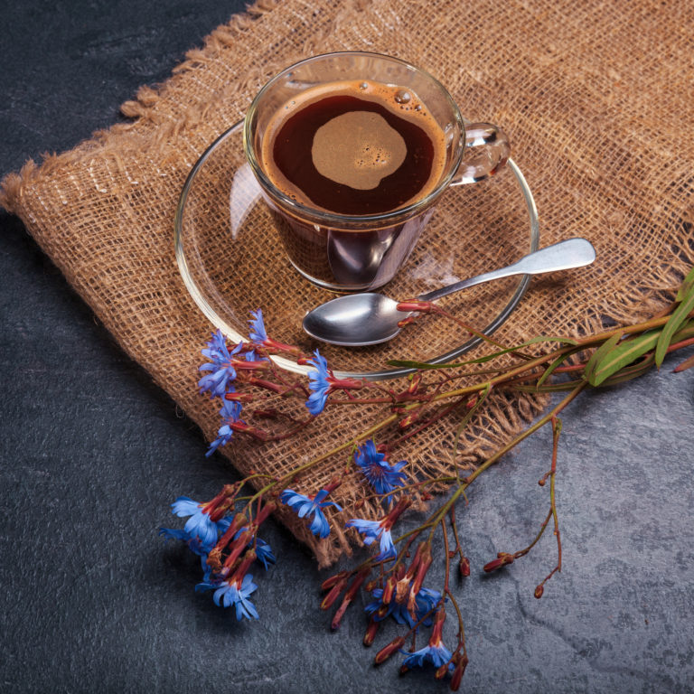 Cup with chicory drink and blue chicory flowers on rustic table