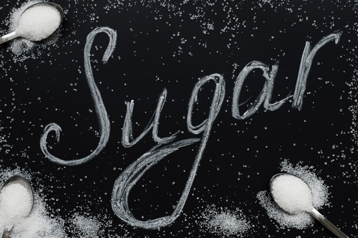 "Sugar eating concept. Refined white sugar in small spoons on black background. Food lettering. The word ""Sugar"""