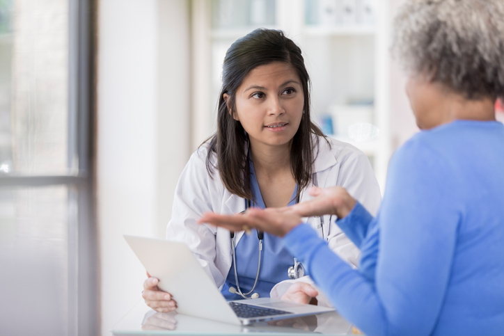 Concerned doctor talking about fibroids with woman.