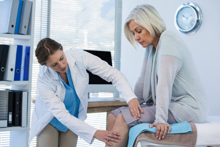 Doctor examining patient knee in clinic
