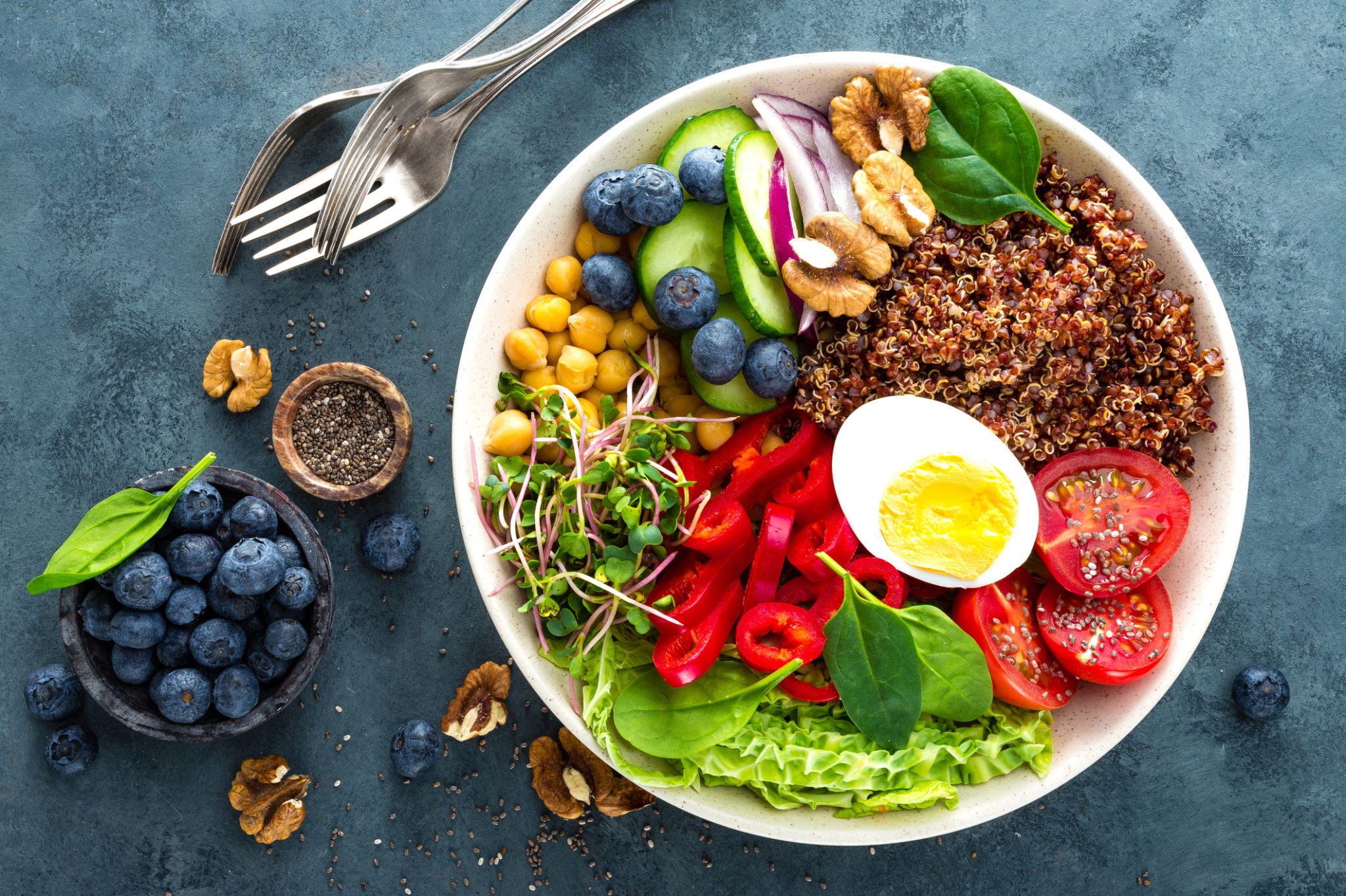 Buddha bowl dinner with boiled egg, chickpea, fresh tomato, sweet pepper, cucumber, savoy cabbage, red onion, green sprouts, spinach leaves, blueberry, walnuts, chia and quinoa. Healthy dish, lunch bowl. Detox diet. Balanced food. Top view