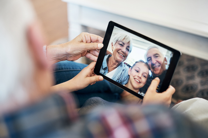 Shot of an adorable little girl using a digital tablet with her grandparents at home