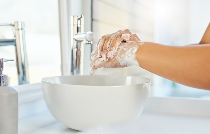 Cropped shot of an unrecognizable young woman washing her hands in the bathroom basin at home