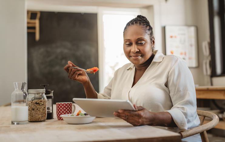 Smiling African American woman sitting at her kitchen table in the morning using a digital tablet while eating a healthy breakfast
