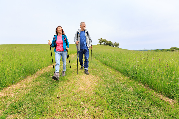Nordic walking - active mature couple enjoying a green nature walk