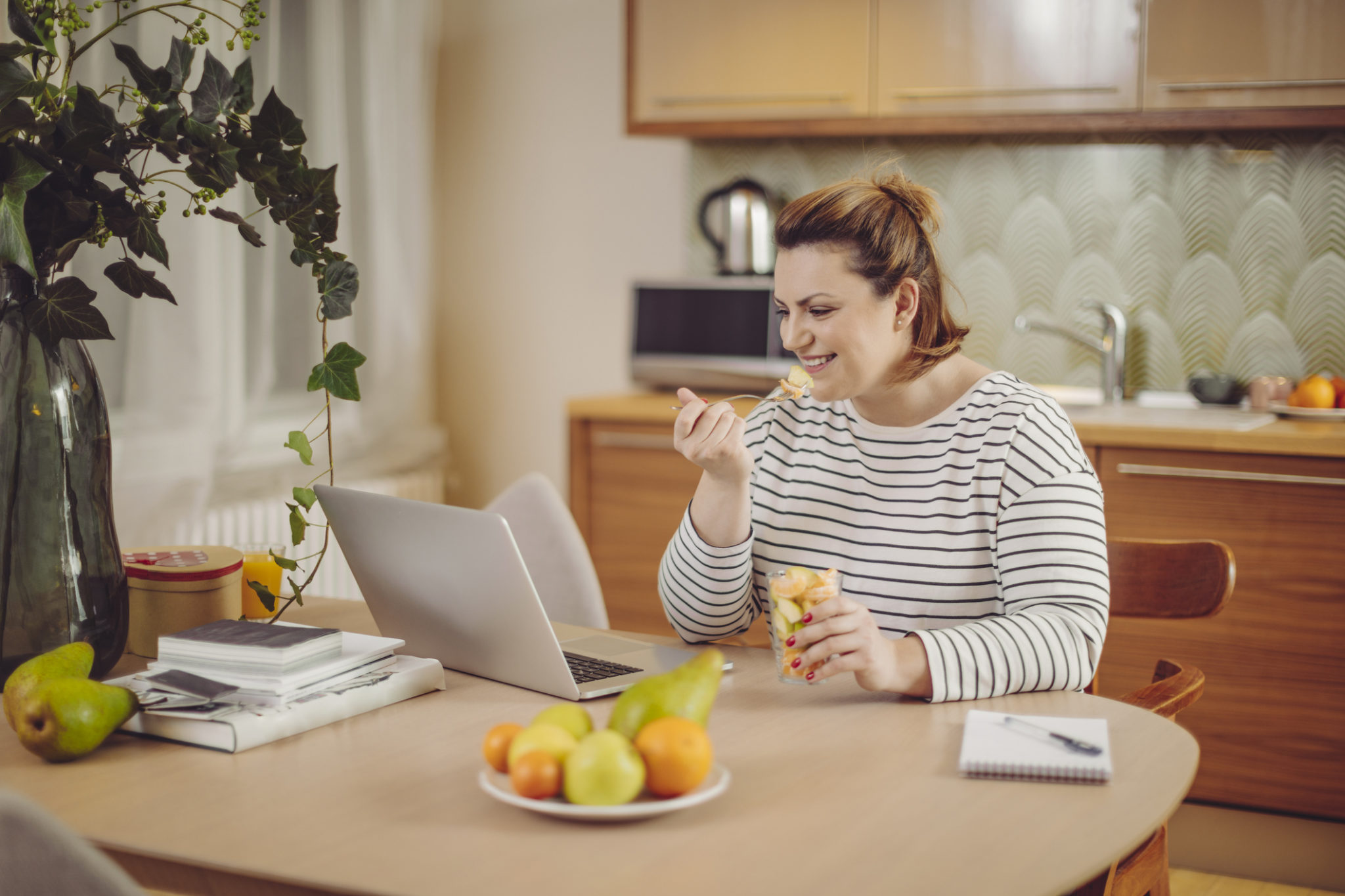 Young woman at home eating healthy fruit and working on her laptop