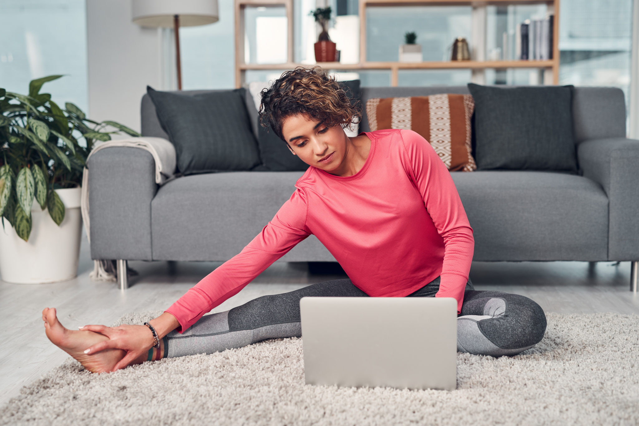 Full length shot of a young woman using a laptop while stretching in her living room