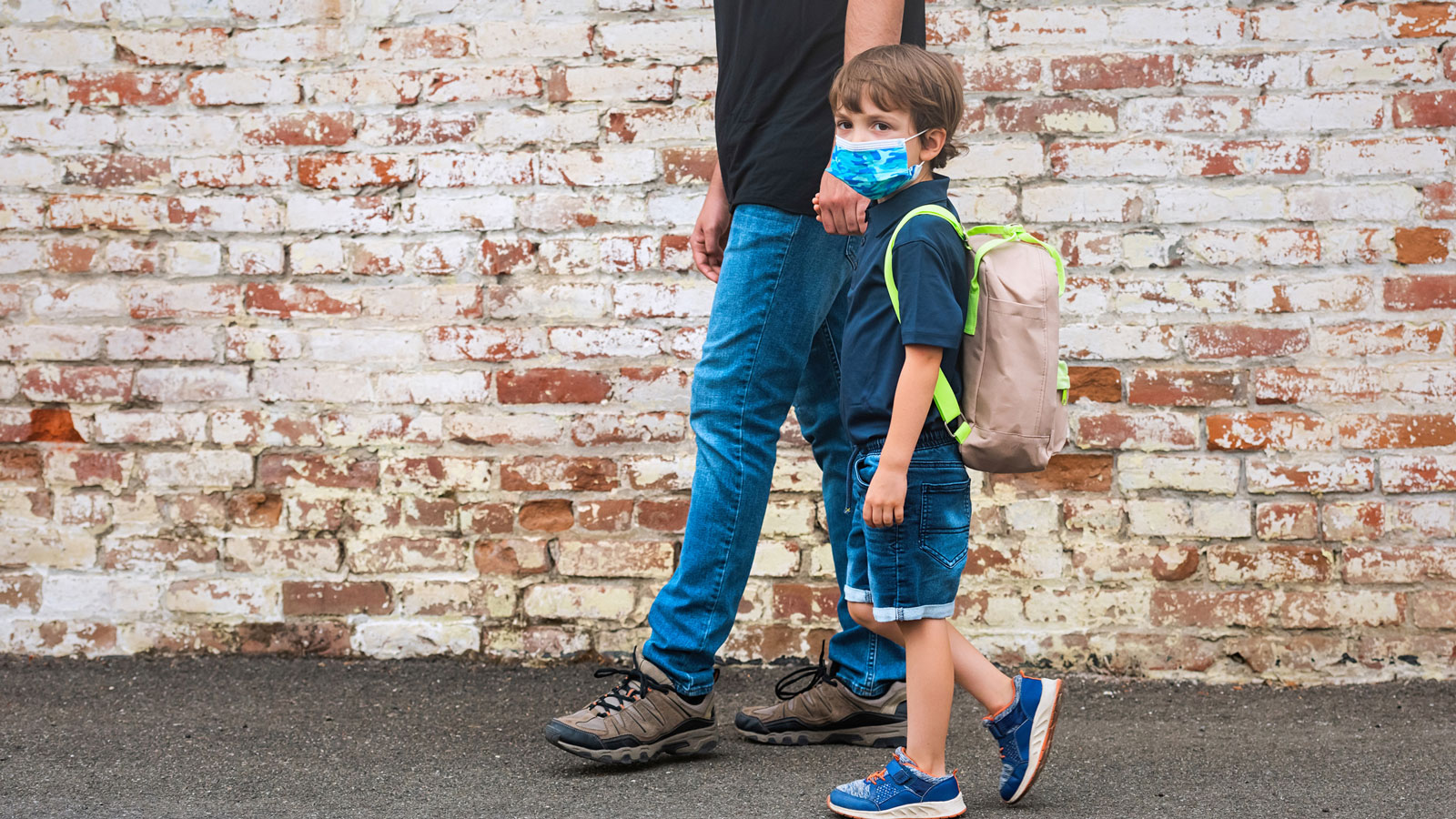 child in a mask with a backpack holding a parent's hand