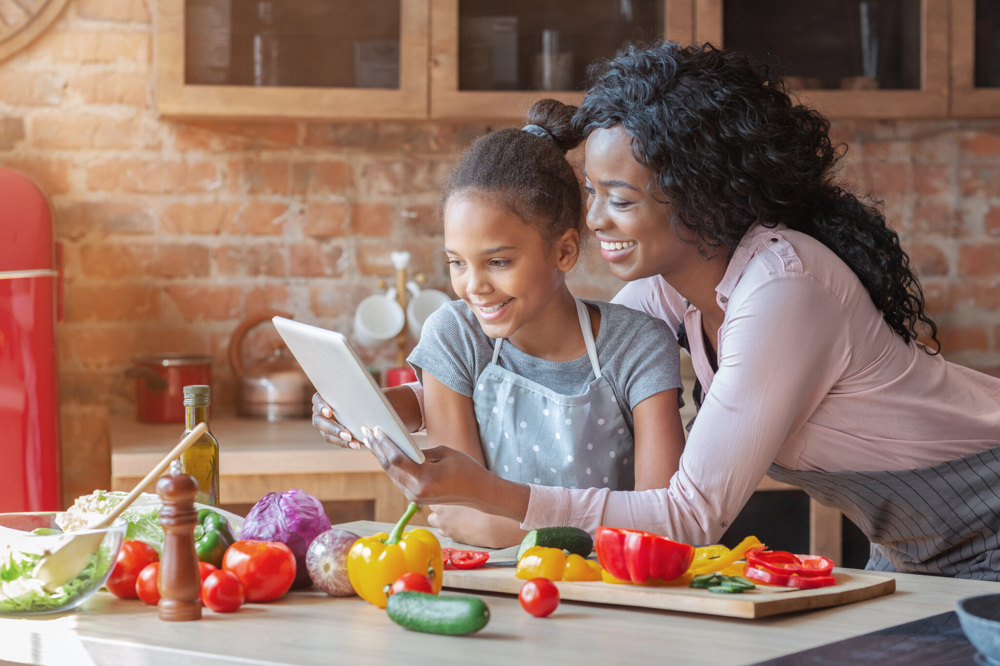 Mommy and daughter reading recipe on tablet at kitchen