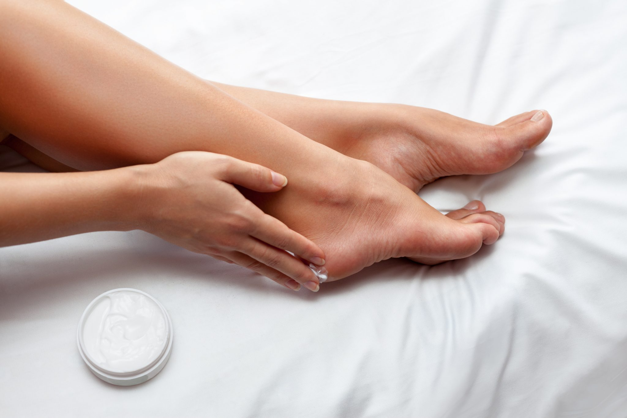 Woman caring about her feet and putting hydrating cream on it
