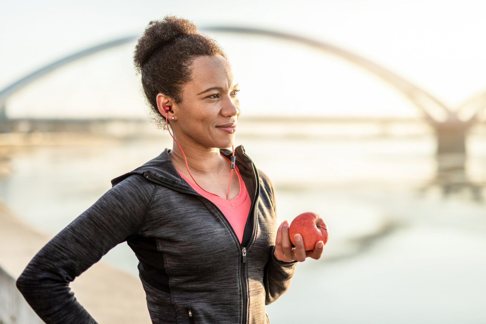 Happy African American Athletic Woman Eating An Apple After Exercise