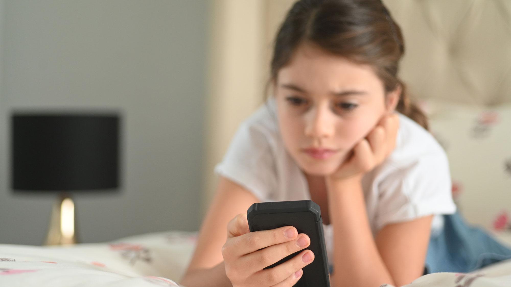 child on smartphone looking sad